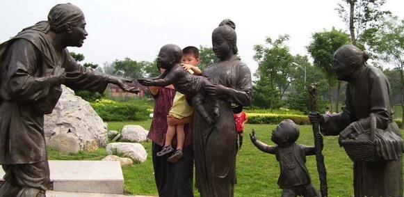 This sculpture is of a child offering an older person some food while a grandmother and another young child watch.  Included in this photo are mother and small child interacting with the sculpture.