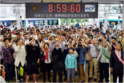 Description: Picture of people taking a picture of a clock with an extra second on it in Tokyo