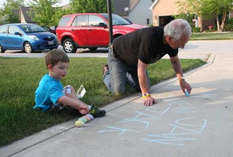 Al and Jack writing in chalk in the driveway