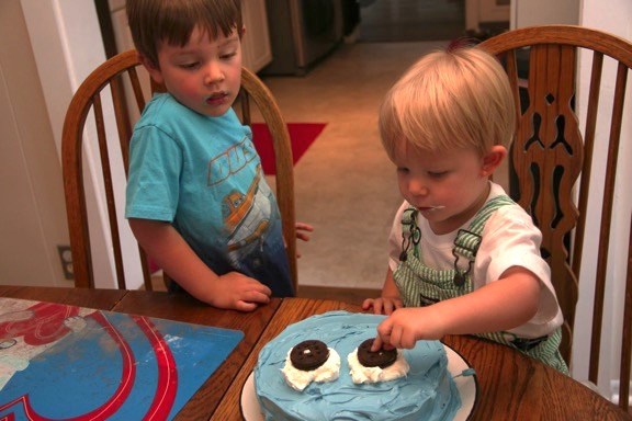 Owen and Jack are finishing their father's birthday cake.